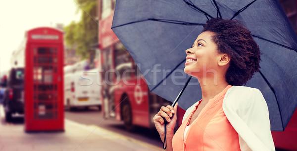 happy african woman with umbrella in london city Stock photo © dolgachov
