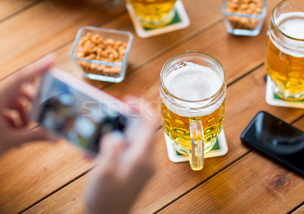 close up of hands with smartphone picturing beer Stock photo © dolgachov