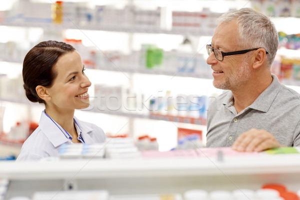 happy pharmacist talking to senior man at pharmacy Stock photo © dolgachov