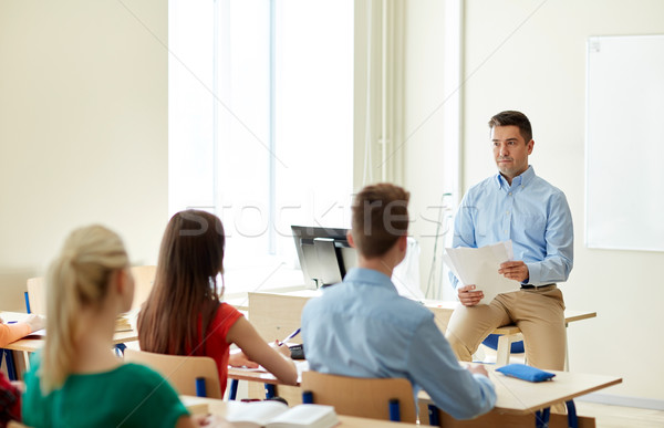 group of students and teacher with papers or tests Stock photo © dolgachov