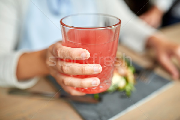 hand with glass of juice at restaurant Stock photo © dolgachov