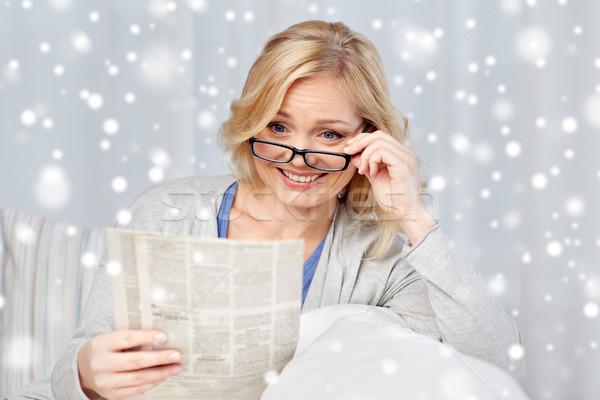 Femme lunettes lecture journal maison nouvelles Photo stock © dolgachov