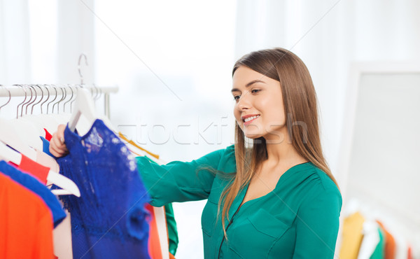 happy woman choosing clothes at home wardrobe Stock photo © dolgachov