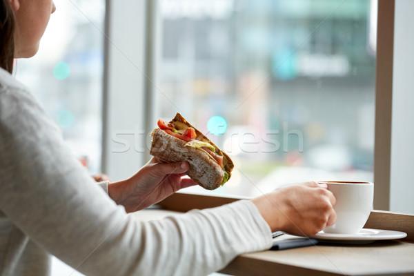 Mulher alimentação sanduíche potável café café Foto stock © dolgachov