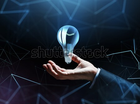 businessman hand with bulb over dark background Stock photo © dolgachov