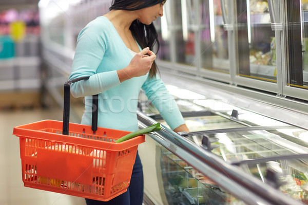 Stock photo: woman with food basket at grocery store freezer