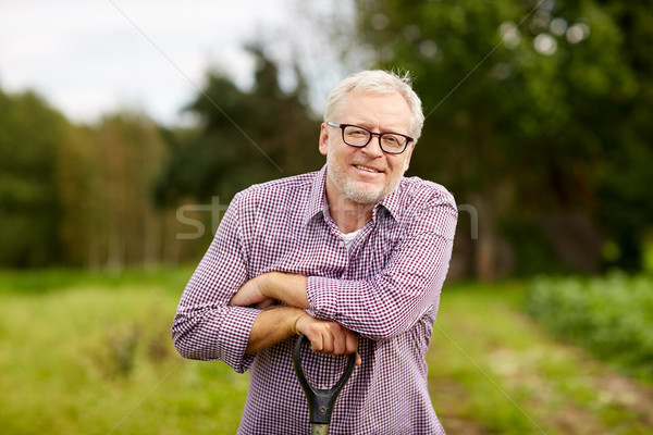 happy smiling senior man with garden tool at farm Stock photo © dolgachov