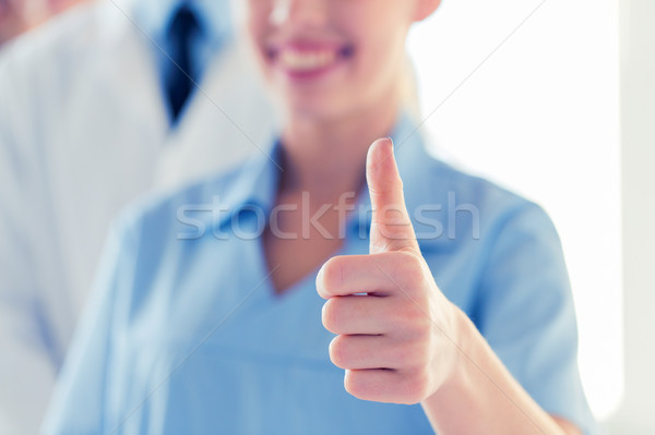close up of doctor or nurse showing thumbs  Stock photo © dolgachov