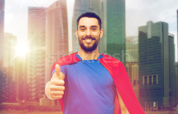 happy man in red superhero cape showing thumbs up Stock photo © dolgachov