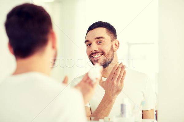 Boldog férfi jelentkezik hab fürdőszoba tükör Stock fotó © dolgachov