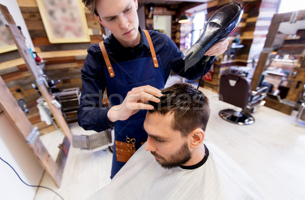 barber with fan drying male hair at barbershop Stock photo © dolgachov