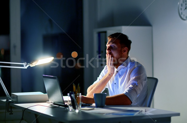 man with laptop and coffee working at night office Stock photo © dolgachov