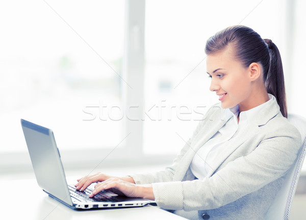 businesswoman with laptop in office Stock photo © dolgachov