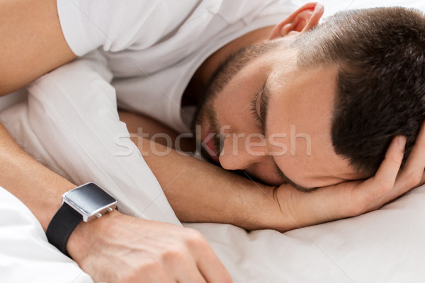 close up of man with smartwatch sleeping in bed Stock photo © dolgachov