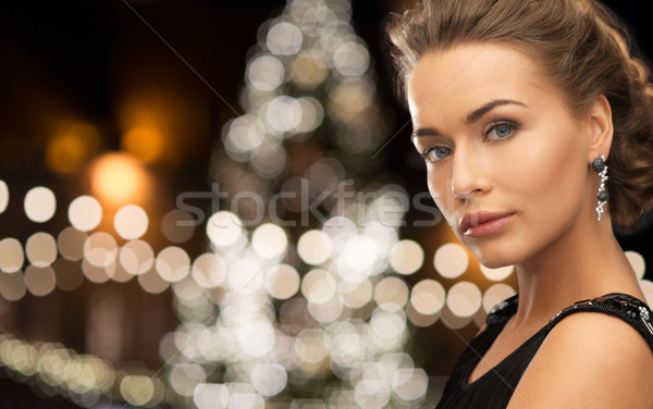 woman wearing jewelry over christmas lights Stock photo © dolgachov