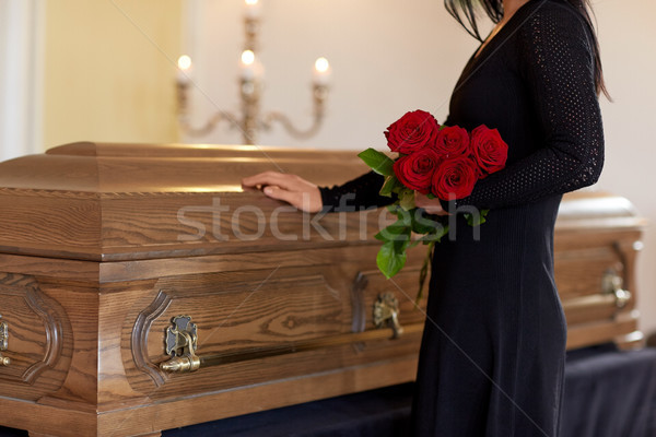 sad woman with red roses and coffin at funeral Stock photo © dolgachov