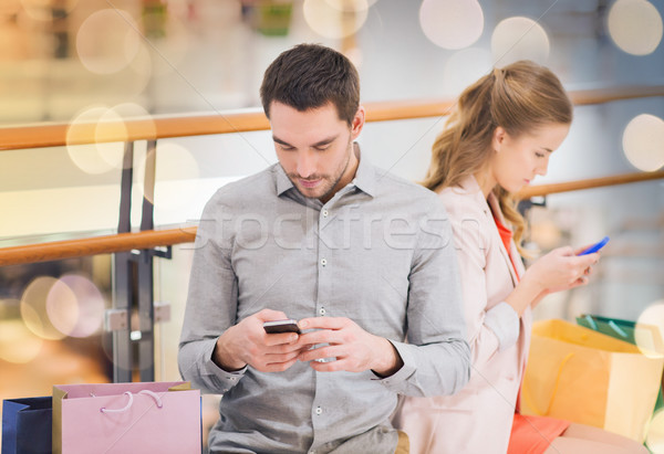 couple with smartphones and shopping bags in mall Stock photo © dolgachov