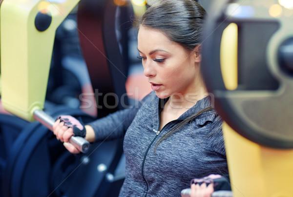 Mulher músculos peito imprensa ginásio máquina Foto stock © dolgachov