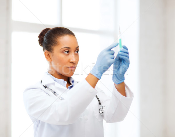 african doctor holding syringe with injection Stock photo © dolgachov