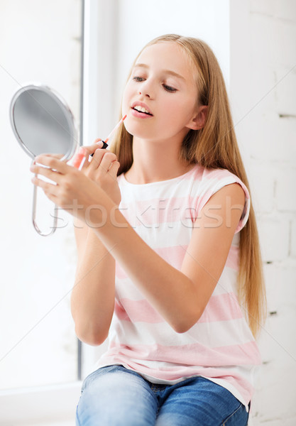 teenage girl with lip gloss and mirror Stock photo © dolgachov