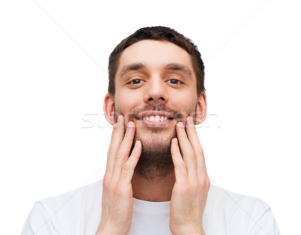 beautiful smiling man touching his face Stock photo © dolgachov