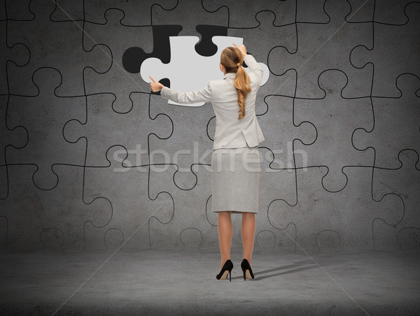 businessman in suit setting piece of puzzle Stock photo © dolgachov