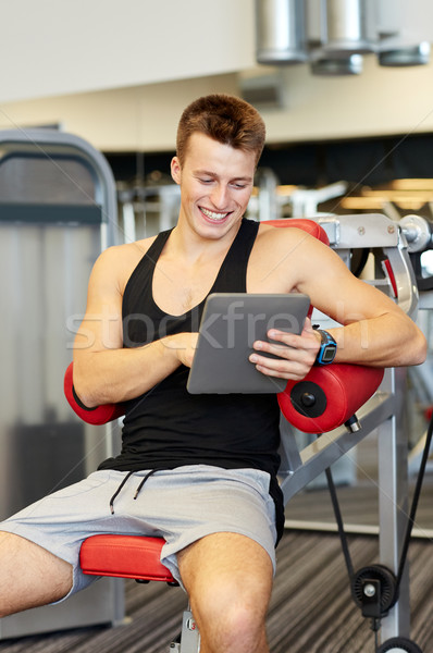 smiling young man with tablet pc computer in gym Stock photo © dolgachov
