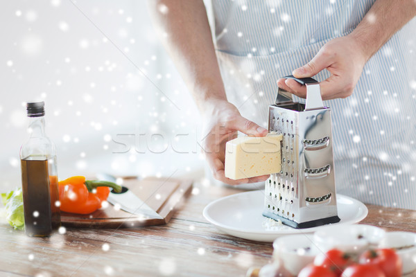 Stock photo: close up of male hands with grater grating cheese