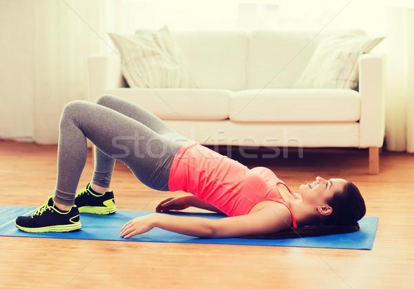 Glimlachend meisje oefening benen zitvlak fitness Stockfoto © dolgachov