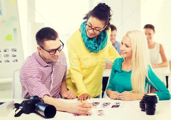 Uśmiechnięty zespołu wydrukowane zdjęć pracy biuro Zdjęcia stock © dolgachov