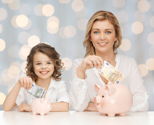mother and daughter putting money to piggy banks Stock photo © dolgachov