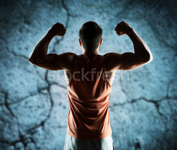 young man or bodybuilder showing biceps Stock photo © dolgachov