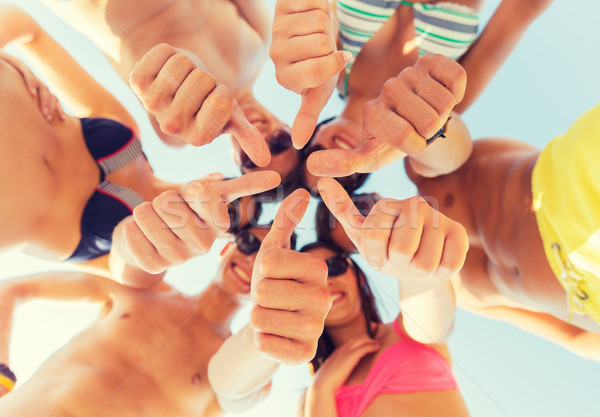 close up of friends showing thumbs in circle Stock photo © dolgachov