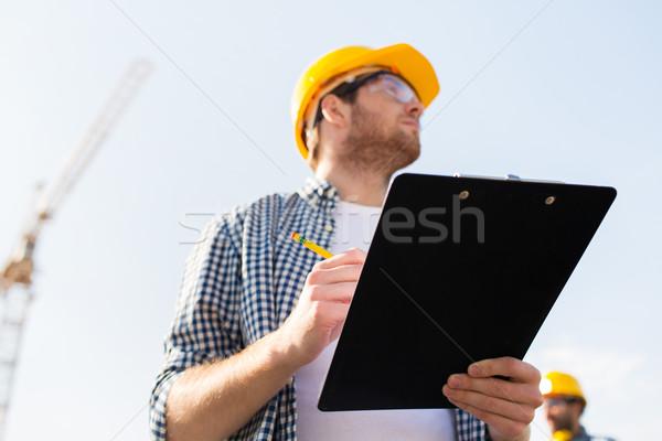 Construtor capacete de segurança clipboard ao ar livre negócio edifício Foto stock © dolgachov