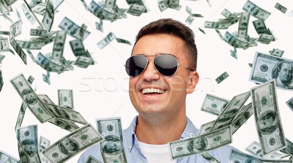 happy man in sunglasses with falling dollar money Stock photo © dolgachov