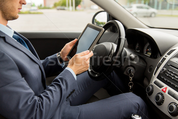 Stock photo: close up of young man with tablet pc driving car