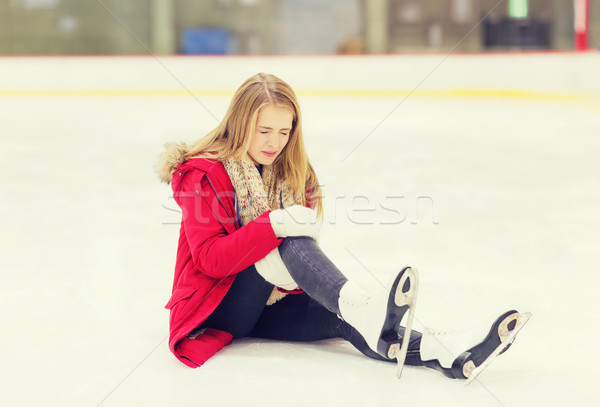 Stock photo: young woman fell down on skating rink