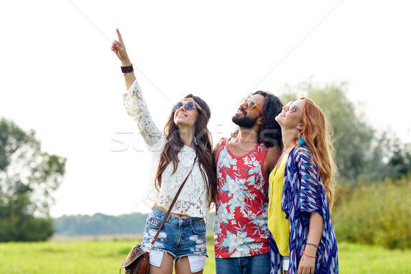 happy hippie friends pointing finger outdoors Stock photo © dolgachov