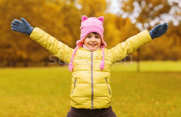 Feliz little girl as mãos levantadas ao ar livre outono infância Foto stock © dolgachov