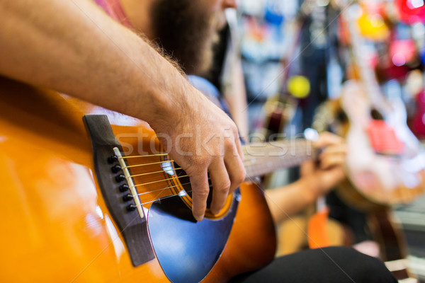 Stock photo: close up of man playing guitar at music store