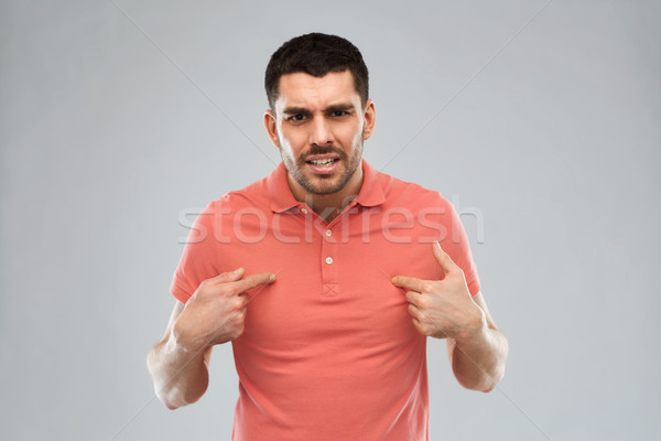 angry man pointing finger to himself over gray Stock photo © dolgachov