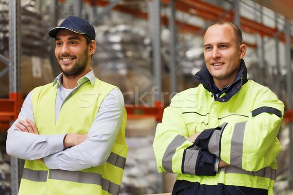 smiling men in reflective uniform at warehouse Stock photo © dolgachov