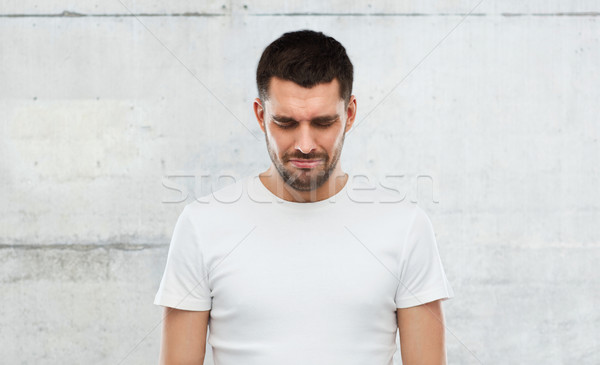 unhappy young man over gray wall background Stock photo © dolgachov