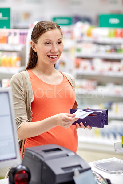 pregnant woman with wallet at cashbox in drugstore Stock photo © dolgachov