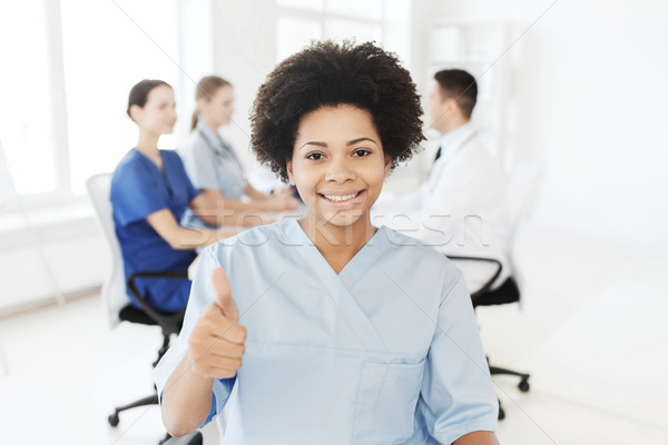 happy female doctor or nurse showing thumbs up Stock photo © dolgachov