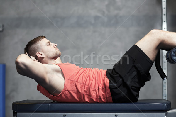 young man making abdominal exercises in gym Stock photo © dolgachov