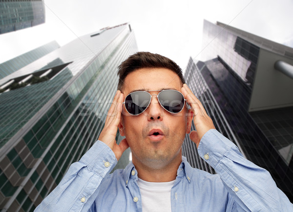 face of scared man in sunglasses over big city Stock photo © dolgachov