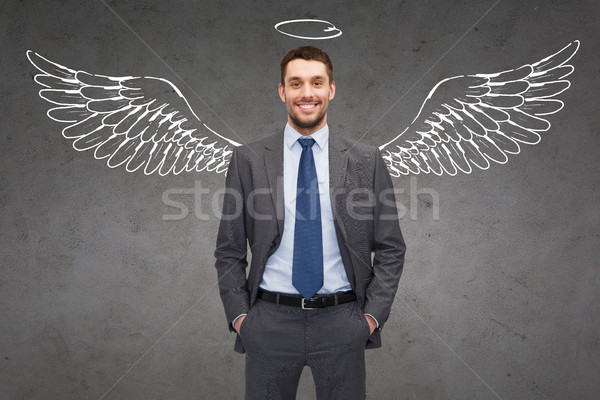 smiling businessman with angel wings and nimbus Stock photo © dolgachov
