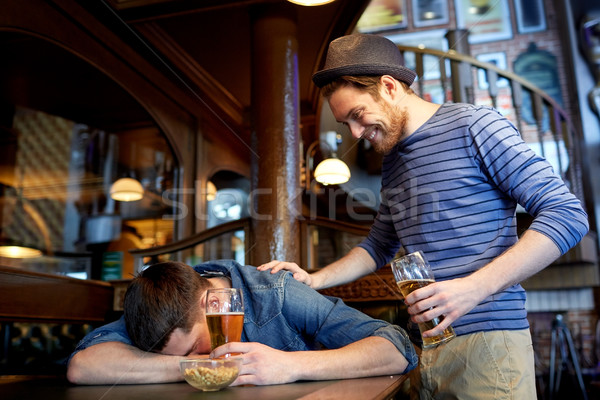 male friends drinking beer at bar or pub Stock photo © dolgachov