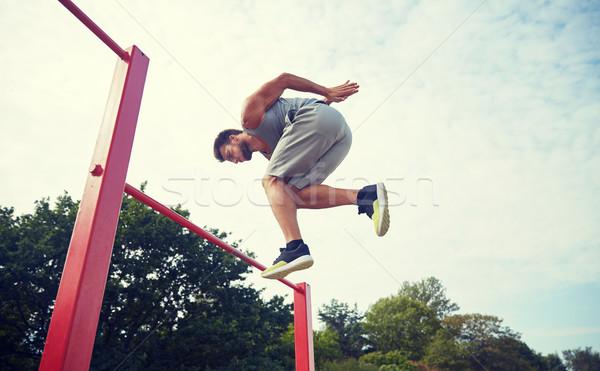 Młody człowiek skoki poziomy bar odkryty fitness Zdjęcia stock © dolgachov